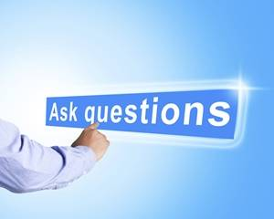 """A person's arm pointing at a sign that says """"Asking Questions"""" - Coaching Questions for Managers"""