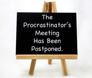 Chalk-Board Sign. The Procrastinators Meeting has been postponed. Stop Procrastinating.