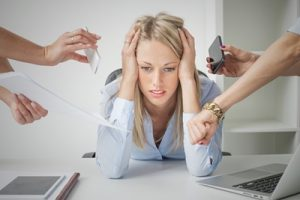 Lady with hands on head and elbows on a desk is looking stressed and overwhelmed as 4 arms try to get her to multitask. The Multitasking Myth.