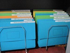Coloured files stored in vertical holder on desk