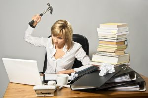 Disorganised and angry business lady hitting a laptop with a hammer. She needs to get organised to reduce stress.