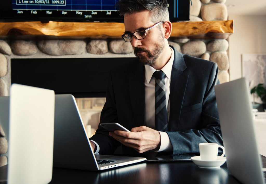 Business man typing on a laptop whilst holding a phone. 4 steps to a clean and stress-free Email Inbox.