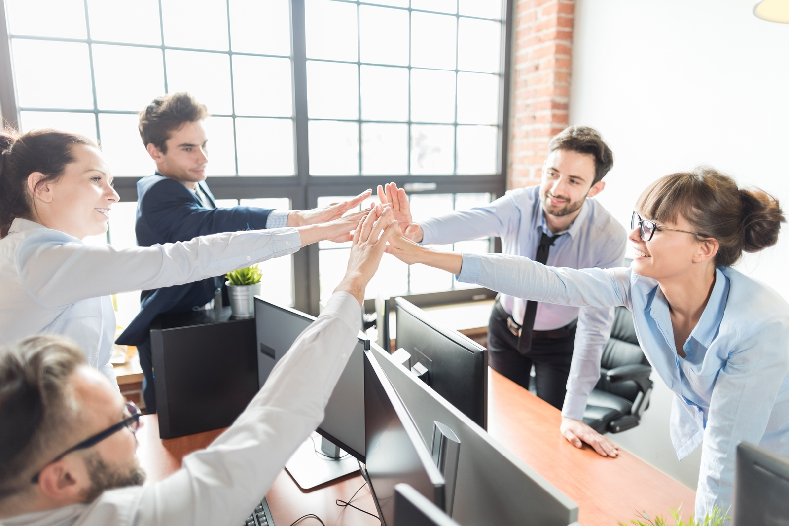 5 people high fiving each other after success. Myers Briggs Team Building