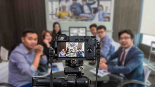 Professional digital Mirrorless camera with microphone recording video blog of Group of asian Business team having video conference,Camera for photographer or Video and Live Streaming concept. Record Microsoft Teams Meeting