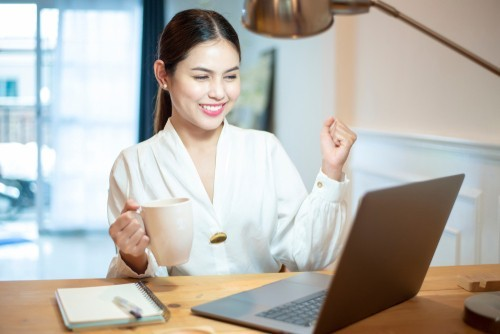 Woman hold coffee clup and clenching fists for success. Advanced Outlook Tools and Tips